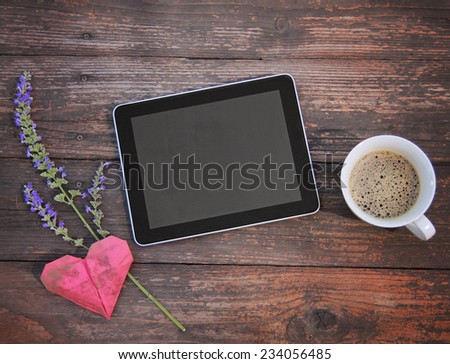 electronic tablet device on a wooden workspace table with coffee and flower - stock photo
