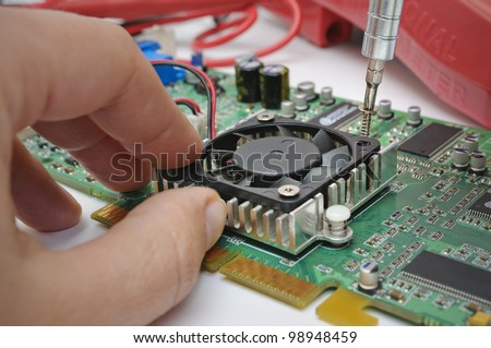 Electronic technician installs a cooler to a computer hardware - stock photo