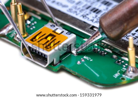 Electronic technician repairs mini USB socket on mobile phone circuit board. Close-up with selective focus and Shallow Depth of Field. Isolated on white background. - stock photo