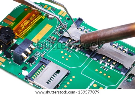 Electronic technician repairs SIM slot on mobile phone circuit board. Close-up with selective focus and Shallow Depth of Field. Isolated on white background. - stock photo