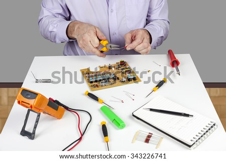 Electronic test engineer using long nose pliers to form a circuit board component on his white topped work bench - stock photo