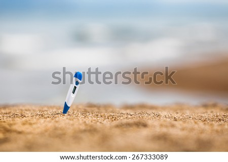Electronic thermometer on a beach - stock photo