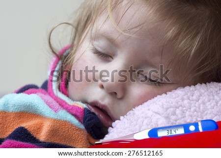 Electronic thermometer showing  temperature and a little sick girl in bed - stock photo