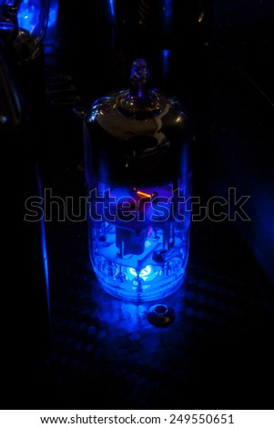 Electronic Vacuum tube of a hi fi amplifier in a dark room: incandesent filament and ionized gas - stock photo