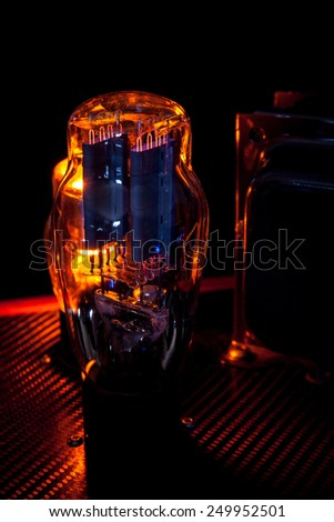 Electronic vacuum tube of hi fi amplifier, in a dark room, with natural cathode luminescence - stock photo