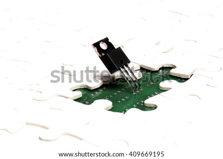 Electronics as a puzzle. Microchip mounted on  circuit board seen through missed part of jigsaw puzzle. Electronics, nanotechnology, microchip concept - stock photo