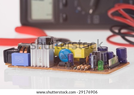 electronics components on board with multimeter - stock photo