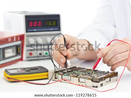 Electronics engineer testing computer part in electronics workshop - stock photo