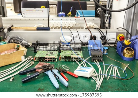 electronics equipment assembly workplace with pliers and necessary tools - stock photo