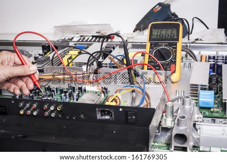Electronics Repair service with red probe and capacitors on electronic board - stock photo