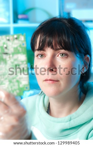 Electronics repair tech examines a circuit board - stock photo