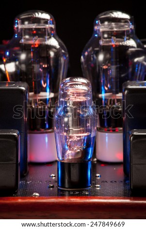 Electronics vacuum tubes of hi fi amplifer, with red wood chassis, in a dark room, with natural luminescence.