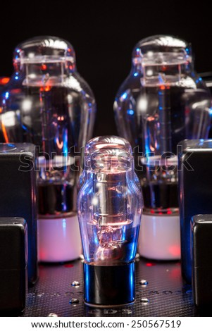 Electronics vacuum tubes of hi fi amplifier with red wood chassis, in a dark room, with natural luminescence - stock photo