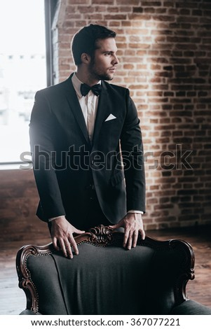 Elegance and confidence. Thoughtful young handsome man in formalwear and bow tie leaning to the chair and looking away while standing in loft interior - stock photo