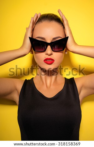 Elegance and style. Studio portrait of gorgeous young woman in sunglasses posing against yellow background. - stock photo