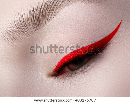 Elegance close-up of beautiful female eye with fashion trend bright colors eyeshadow and eyeliner. Macro shot of beautiful woman's face part with makeup. Cosmetics, beauty and make-up - stock photo