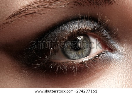 Elegance close-up of female eye with dark gray eyeshadow. Macro shot of beautiful woman's face part. Wellness, cosmetics and make-up. - stock photo