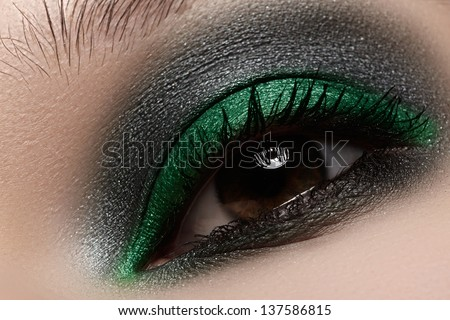 Elegance close-up of female eye with green and black color eyeshadow. Macro shot of beautiful woman's face part. Wellness, cosmetics and make-up. - stock photo