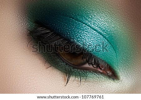 Elegance close-up of female eye with mint color eyeshadow. Macro shot of beautiful woman's face part. Wellness, cosmetics and make-up.