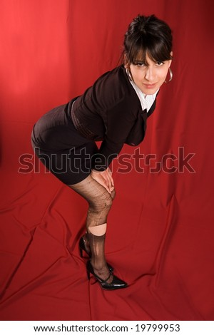 Elegance dressed woman with provocative ripped stocking on red textile backgrounds