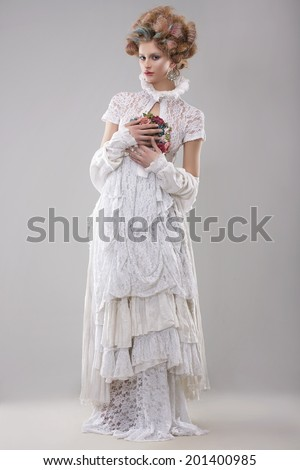 Elegance. Gorgeous Fashion Model in Long Gown and Bouquet of Flowers - stock photo