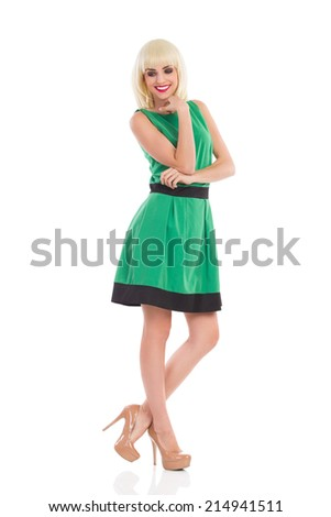 Elegance smiling blonde woman in a green dress posing with hand on chin and looking away. Full length studio shot isolated on white. - stock photo