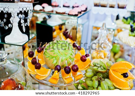 Elegance wedding reception table with food and decor. Carved melon with other fruits