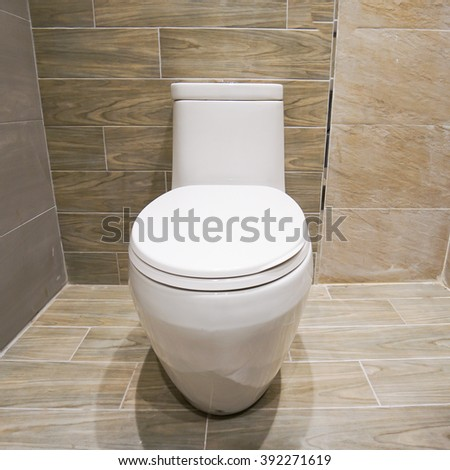 elegance white ceramic toilet in stone tiled bathroom. - stock photo
