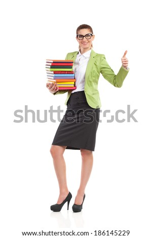 Elegance woman in green suit jacket, black skirt and glasses holding a stack books and showing thumb up. Full length studio shot isolated on white. - stock photo