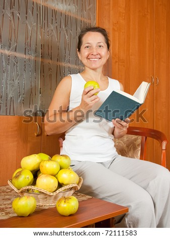 elegance woman reading bok near table with apples - stock photo