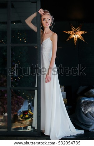Elegance young Beautiful model woman in white dress and with blue eyes standing near the window in black loft interior. Russian model.