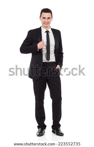 Elegance young handsome man posing in black suit. Full length studio shot isolated on white. - stock photo