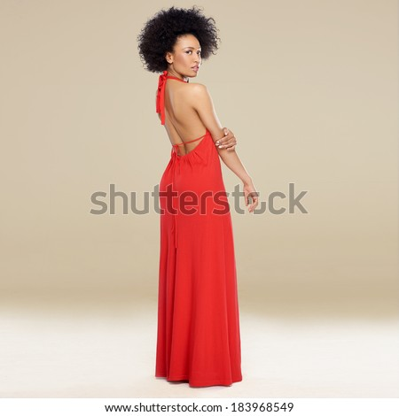 Elegant African American woman with an afro hairstyle posing in a red evening gown standing sideways looking over her shoulder - stock photo