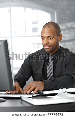 Elegant afro businessman concentrating on working on computer at office desk. - stock photo