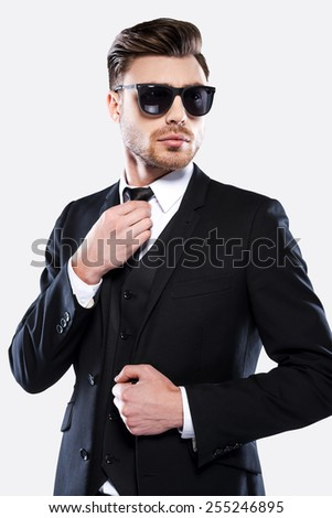 Elegant and charming. Portrait of handsome young man in formalwear and sunglasses adjusting his necktie while standing against grey background - stock photo