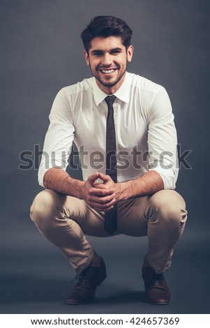 Elegant and cheerful. Full length of confident young handsome man looking at camera with smile while sitting crouched against grey background - stock photo