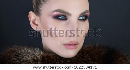 Elegant and chic portrait of a woman wearing the fur, studio shot over dark background