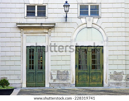 Elegant and classical building facade with two green painted door - stock photo