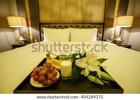 Elegant and comfortable home & hotel bedroom interior as background, A glass of milk,bananas and grapes with lily flowers at bed. - stock photo