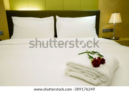 Elegant and comfortable home & hotel bedroom interior as background, the red carnation flowers and bath towel at bed, romantic style. - stock photo