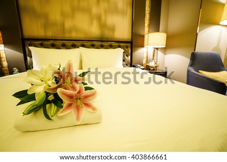 Elegant and comfortable home & hotel bedroom interior as background, the red & white lily flowers at bed, romantic style.