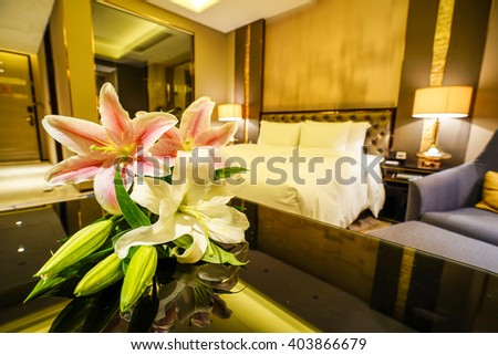 Elegant and comfortable home & hotel bedroom interior as background, the red & white lily flowers at bed, romantic style. - stock photo