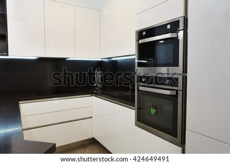 Elegant and comfortable kitchen interior, white glossy facades and built in appliances. Kitchen electrical equipment. Cooker and oven, black cooking worktop. Modern interior design.  - stock photo