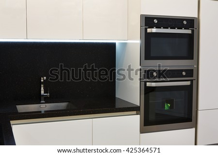 Elegant and comfortable kitchen interior, white glossy facades and built in appliances. Kitchen electrical equipment. Cooker and oven, sink and black cooking worktop. Modern interior design.