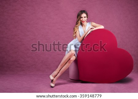 Elegant and fashion woman holding heart - stock photo
