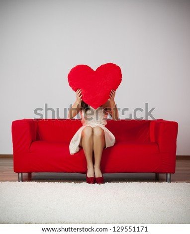 Elegant and fashion woman holding heart shape pillow - stock photo