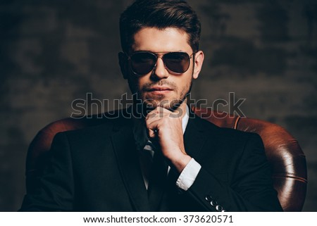 Elegant and perfect.Portrait of young handsome man in suit holding hand on chin and looking at camera while sitting in leather chair against dark grey background - stock photo