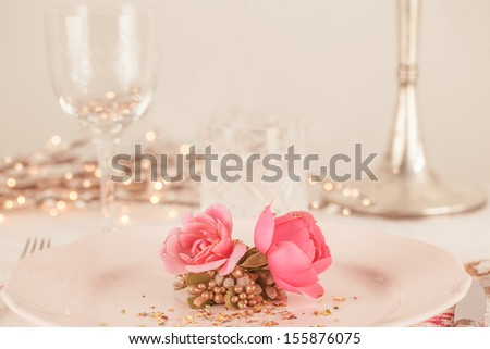 Elegant and romantic dinner setting with rose decoration and lights - stock photo