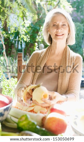 Elegant and smart mature woman sitting in a home garden preparing vegetarian food and peeling a red apple while relaxing and smiling during a sunny day, outdoors. - stock photo