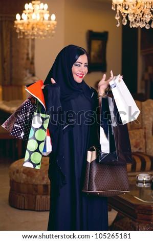 elegant arabian lady with hijab holding shopping bags - stock photo